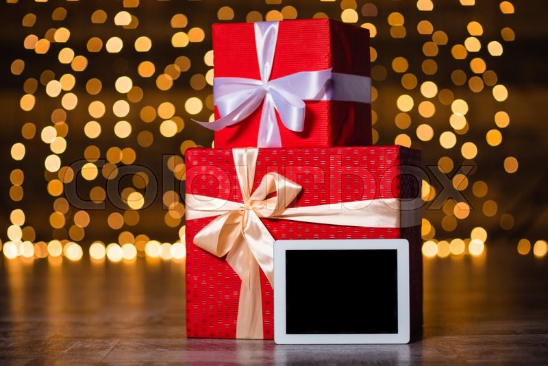 Gift boxes and tablet computer with blank screen standing on the floor over holidays lights background, stock photo