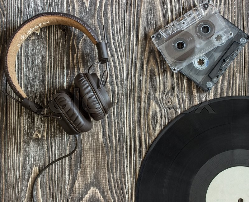 The musical equipment headphones audio cassette and plate lie on a wooden table. Background Top view, stock photo