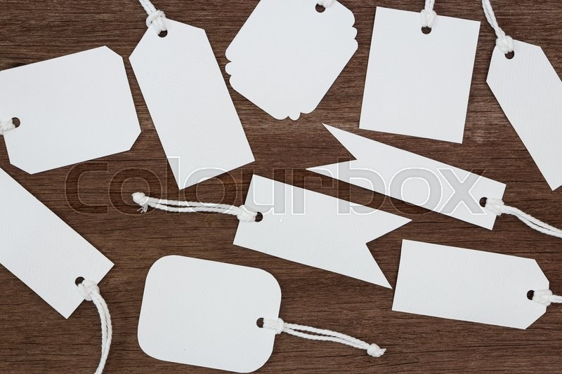 Blank white paper tags label on wood background, stock photo