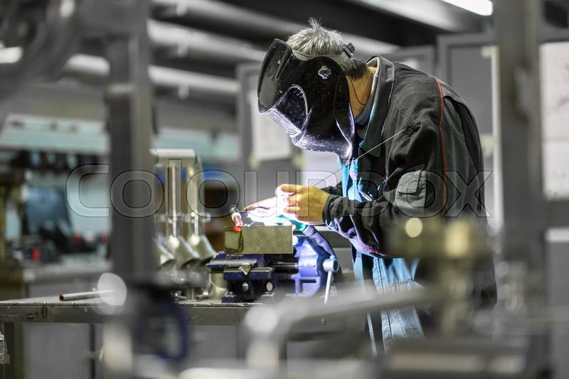 Industrial worker with protective mask welding inox elements in steel structures manufacture workshop, stock photo