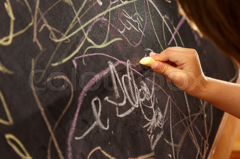 Child\'s hand drawing with chalk on blackboard, stock photo