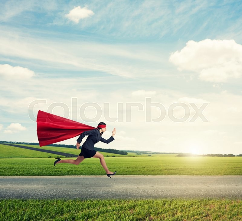 Concentrated superwoman in formal wear and red cloak with mask fast running on the road at outdoor, stock photo