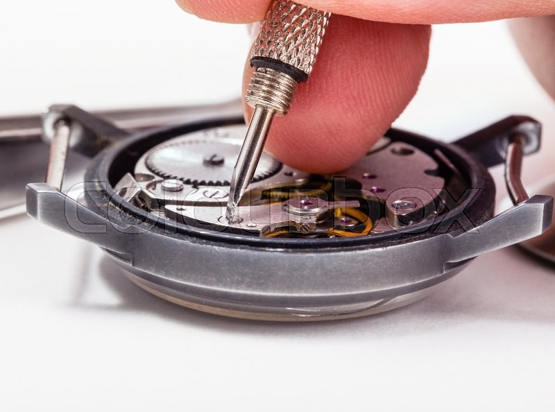 Adjusting old mechanic wristwatch - watch repairer repairs old watch close up, stock photo