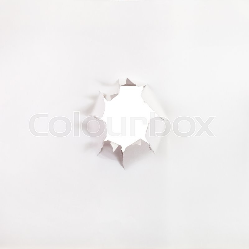 Front view of sheet of paper with rough punched hole, stock photo