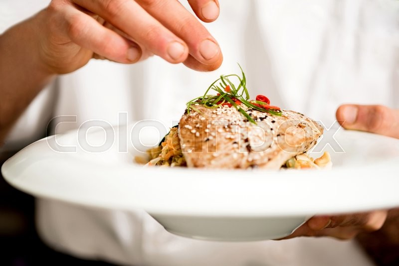Chef adding final touch to tuna appetizer, stock photo
