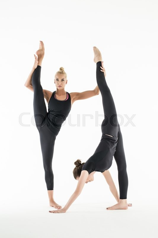 Two Flexible Girl In A Black Leggings Perform Complex