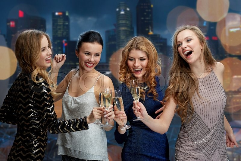 Celebration, friends, bachelorette party, nightlife and holidays concept - happy women clinking champagne glasses and dancing over night city lights background, stock photo