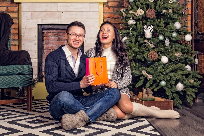 trendy young couple laughing with surprise christmas present clock at midnight time gifts girl gave guy gift orange package