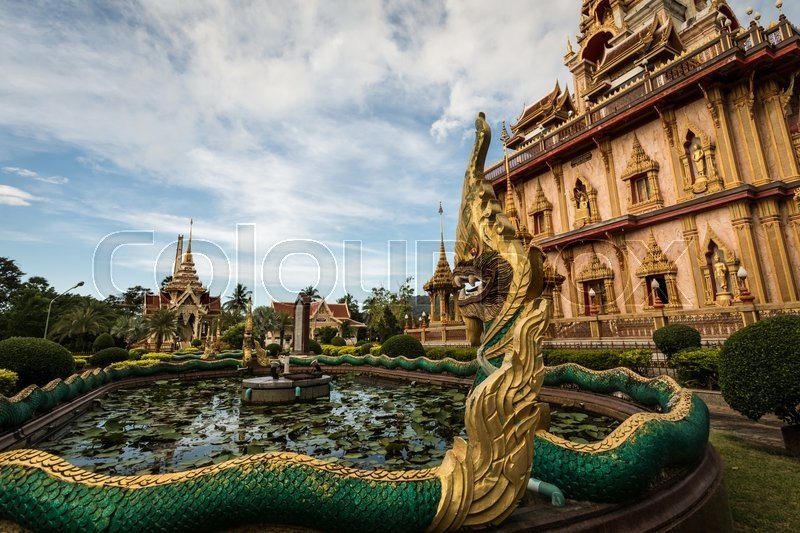 Naga sculpture in the garden of chalong temple under dramatic blue sky, Phuket, Thailand, stock photo