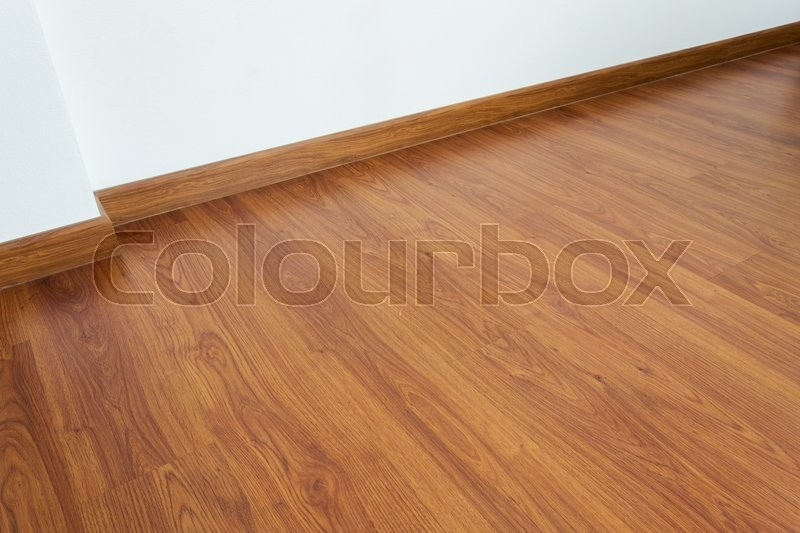 Empty room with brown wood laminate floor and white mortar wall background, stock photo