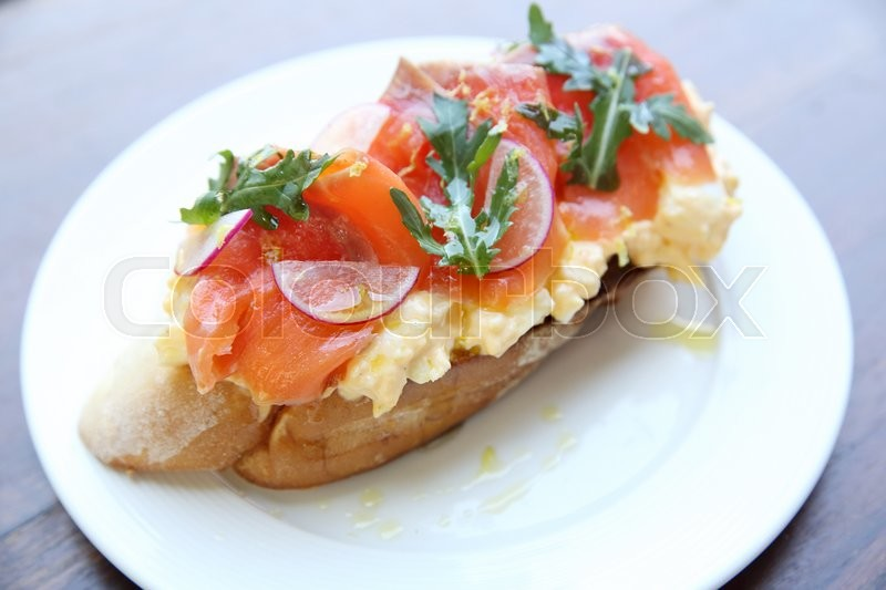 Scrambled Eggs With Smoked Salmon And Whole Wheat Toast Stock Photo