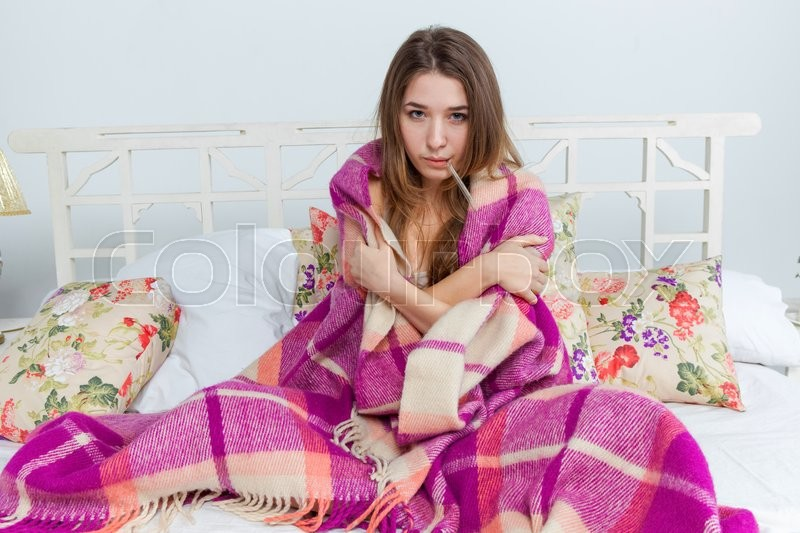 Young sick woman in blanket with thermometer in bed at home, stock photo