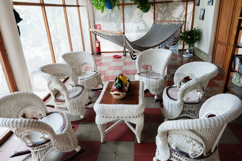 Rattan furniture chair and table with hammock in a room inside a colonial house in Granada Nicaragua, stock photo