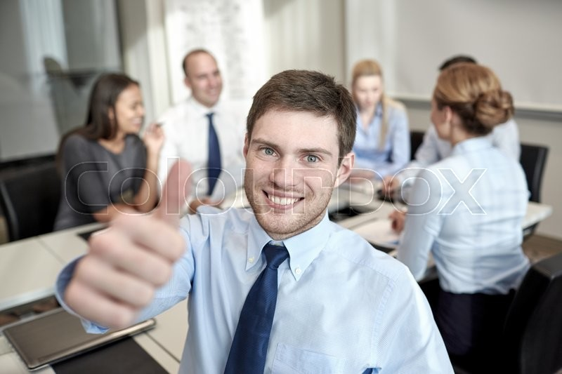 Business, people, gesture and teamwork concept - smiling businessman showing thumbs up with group of businesspeople meeting in office, stock photo