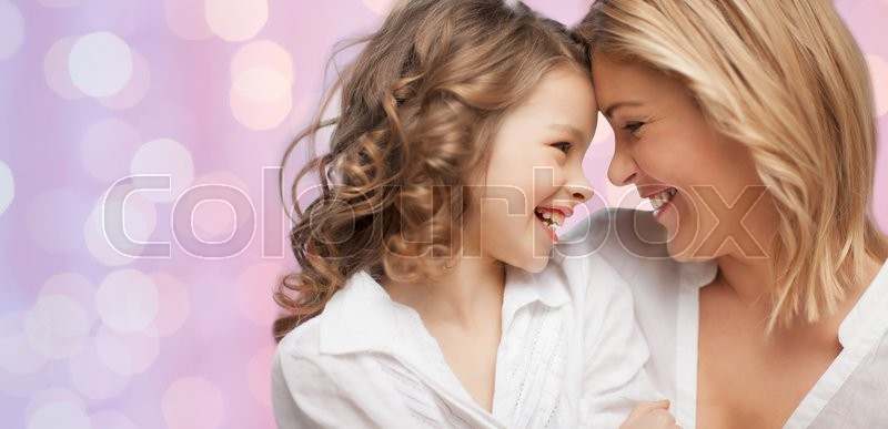 People, motherhood, family, holidays and adoption concept - happy mother and daughter hugging over holidays lights background, stock photo