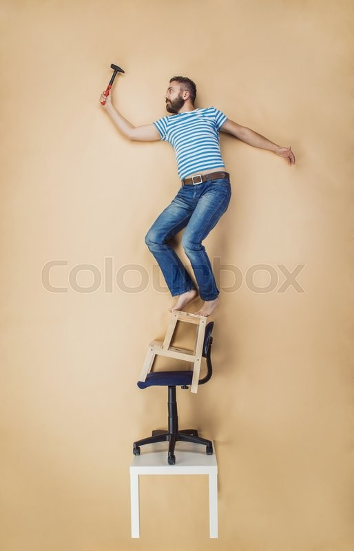 Handyman Standing Dangerously On A Pile Of Chairs Studio