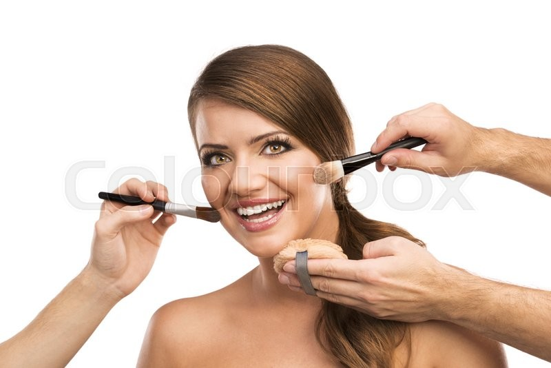 Portrait of beautiful woman with makeup brushes near attractive face, many hands applying make up on woman face isolated on white background, stock photo