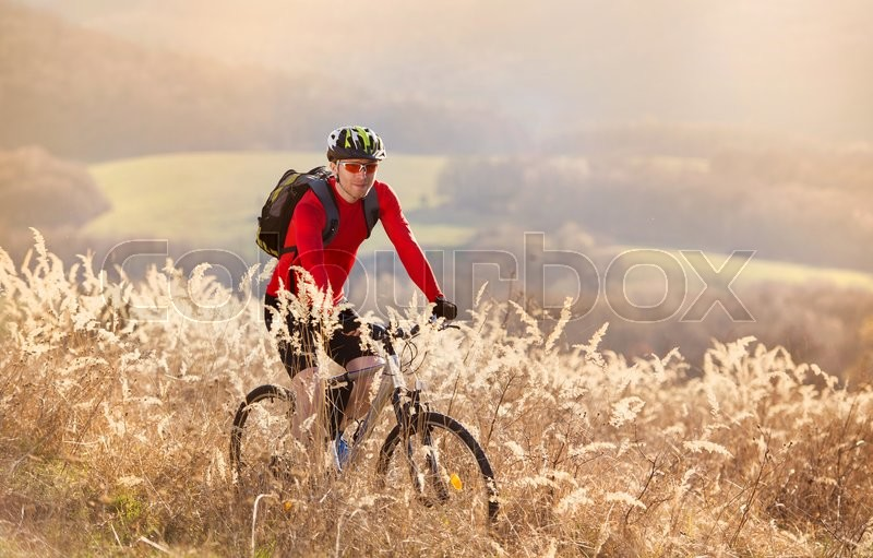 Cyclist man riding mountain bike on outdoor trail in nature, stock photo