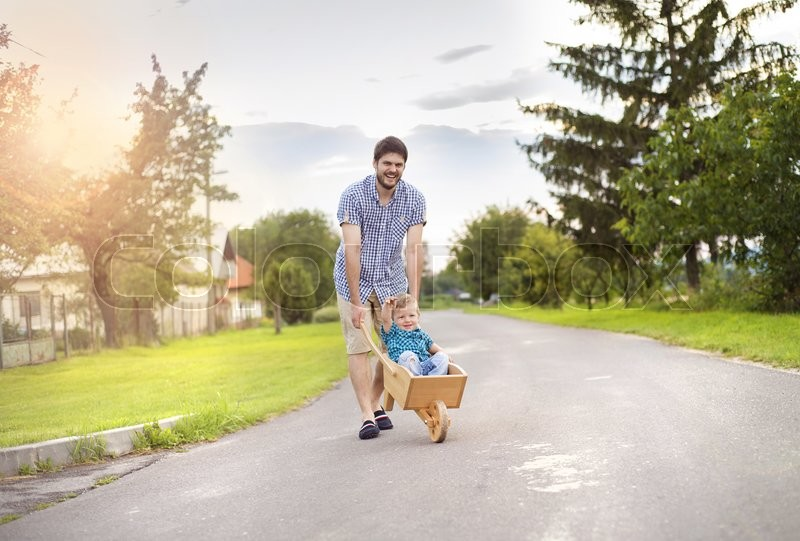 Young Father Pushing His Little Son In Stock Image