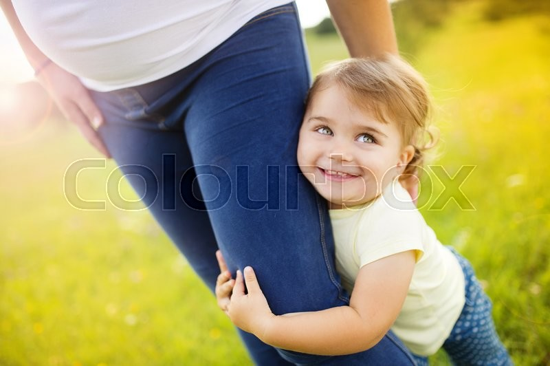 Portrait of happy little daughter holding her pregnant mother´s hand in the park, stock photo