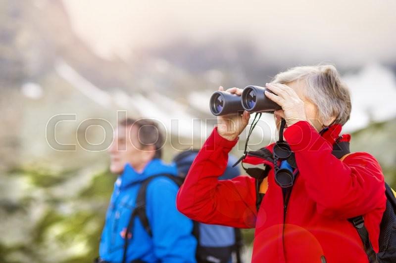 Senior hikers couple enjoying the landscape view with binoculars, stock photo