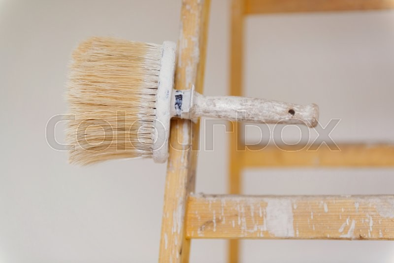 Preparing to paint the wall. Detail of paintbrush on ladder, stock photo