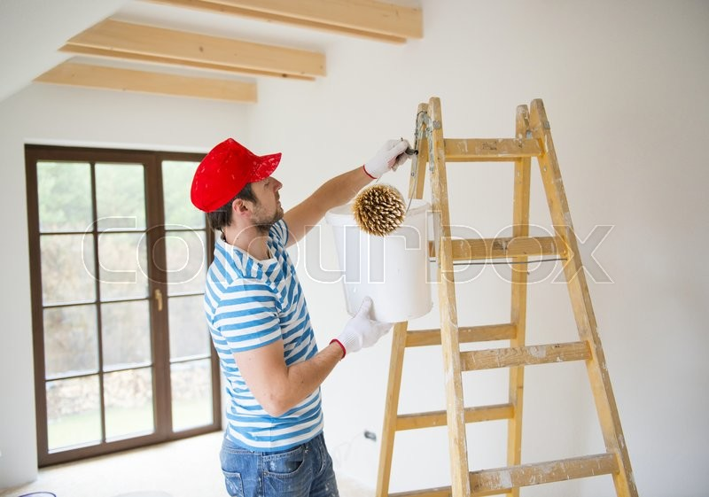 Happy smiling man painting the walls of new home with paintbrush, stock photo