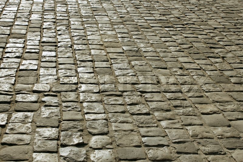 Part of urban square covered with cobblestone. Sunlight reflected on the stones, stock photo