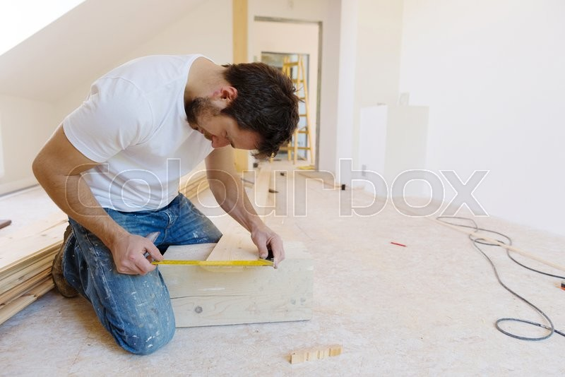 Handyman installing wooden floor in new house, stock photo