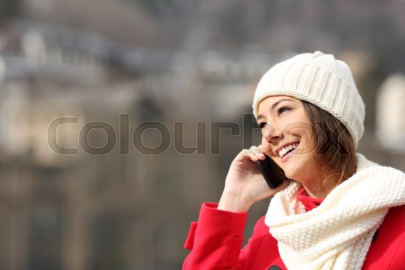 Girl talking on the mobile phone warmly clothed in winter, stock photo