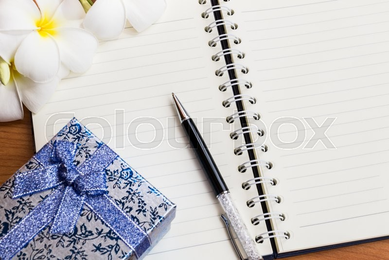 Gift box and pen on notebook with flower on wooden table, stock photo