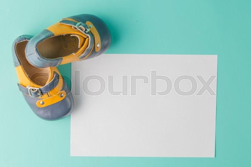 Baby birthday invitation. Vintage leather booties on aquamarine background, stock photo