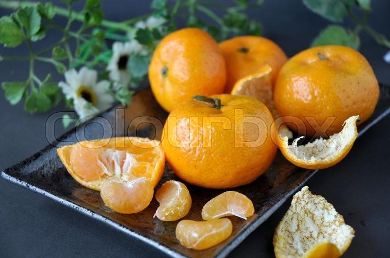 Close up fresh oranges peeled put on black plate, stock photo