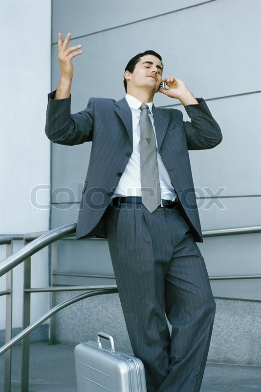 businessman leaning against railing and using cell phone making