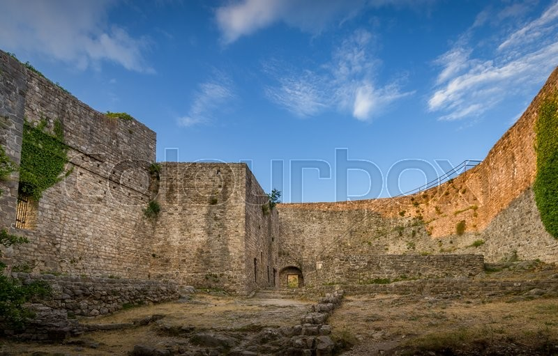 Medieval fortress high stone walls with green plants. Town of Bar citadel, Montenegro, stock photo