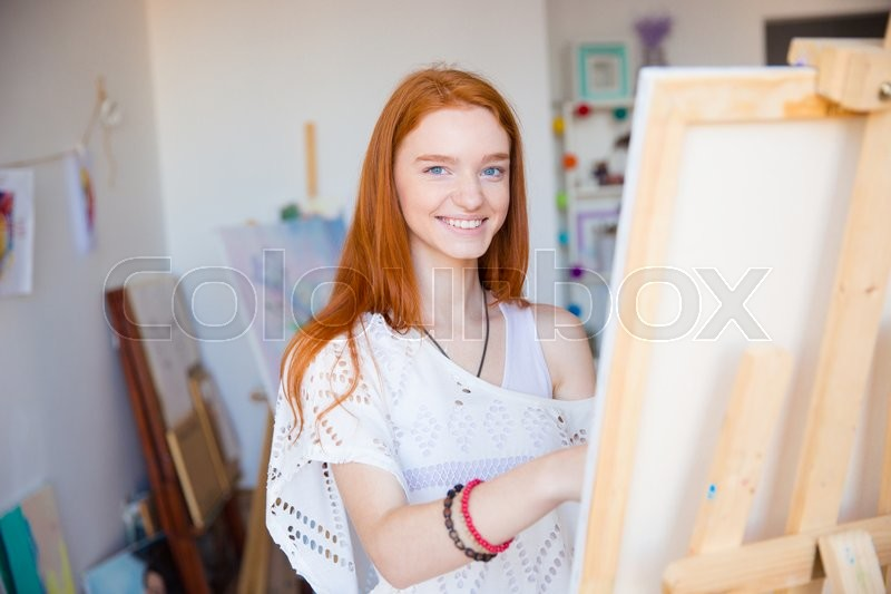 Cheerful attractive woman artist painting on canvas in art workshop, stock photo