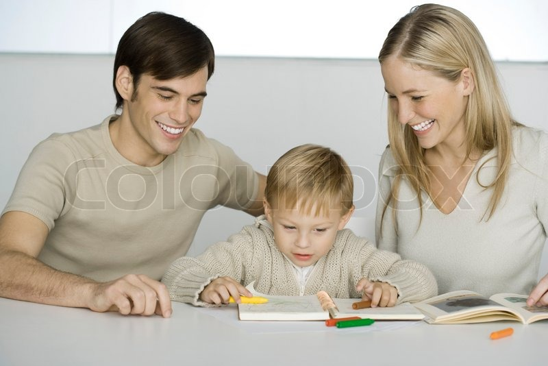 Little Boy Sitting At Table With Parents Coloring Crayons