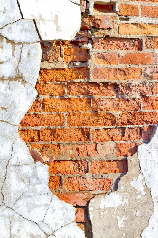 Old brick wall with crumbling plaster cracked