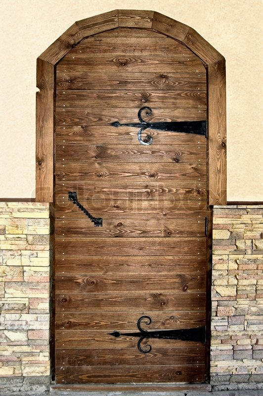 Brown Wooden Door With Black Metal Handles And Hinges On A