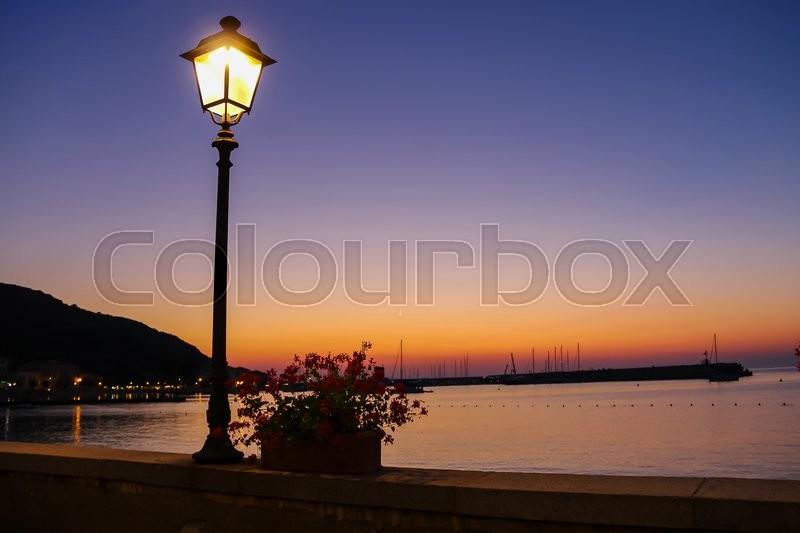 Lighted lantern on coast of the Tyrrhenian Sea on the sunset. Elba Island, Italy, stock photo