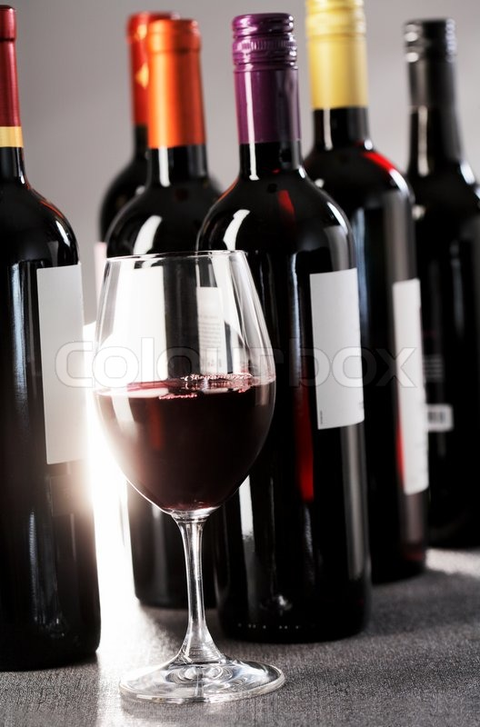 A glass of red wine and bottles in the background stock for Red glass wine bottles suppliers