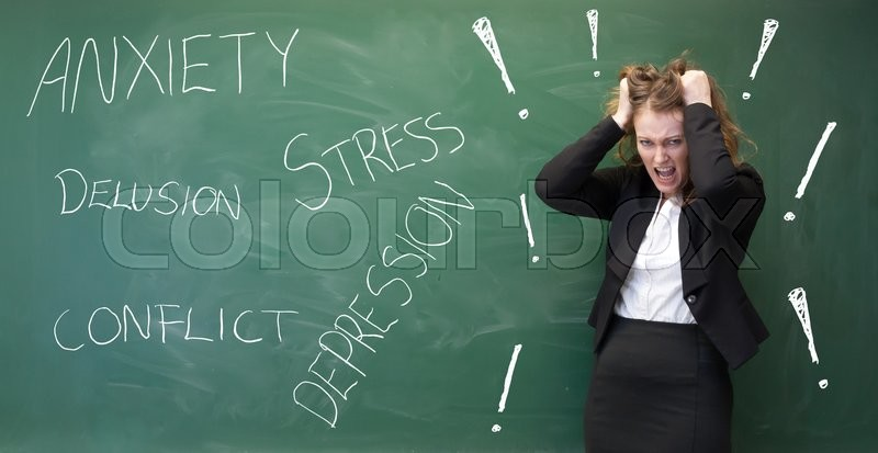 Woman having an anxiety attack in front of a black board, stock photo