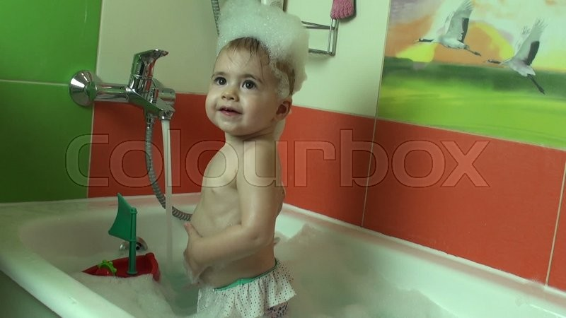 Child taking bath. Little baby in a bath tub washing hair with ...
