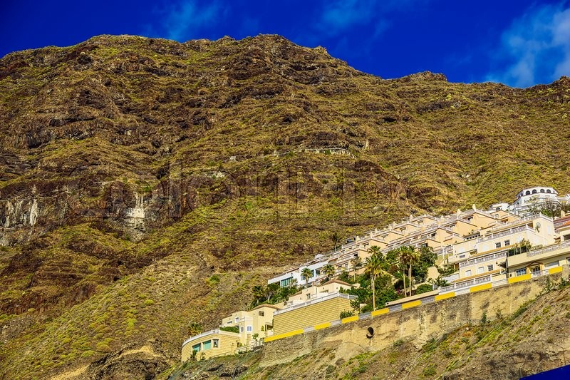 Small Village and Buildings in Green Mountains Landscape on Tenerife Island in Spain at Day, stock photo