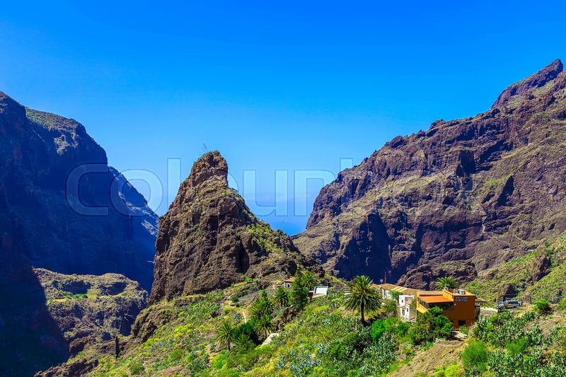 Small Village and Buildings in Green Mountains Landscape on Tenerife Canary Island in Spain at Day, stock photo