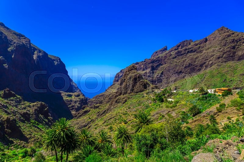 Small Village and Buildings in Green Mountains Landscape on Tenerife Island at Day, stock photo