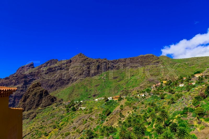 Small Village and Buildings in Green Mountains Landscape on Canary Island at Day, stock photo