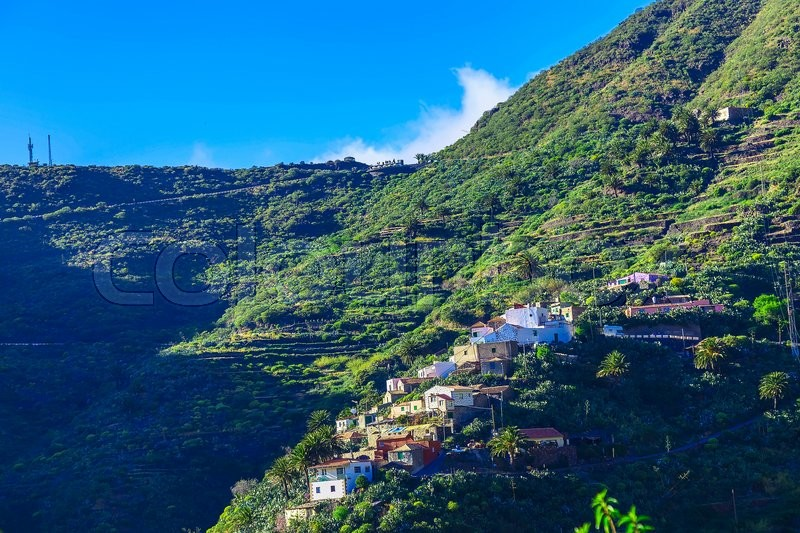 Small Village and Buildings in Green Mountains Landscape on Tenerife Canary Island at Day, stock photo