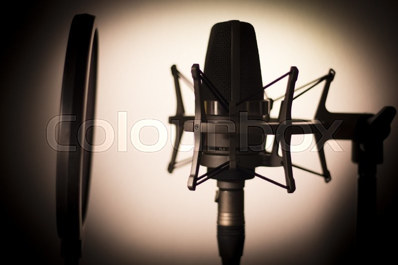 Audio recording vocal studio voice microphone silhouette with anti shock mount and built in anti pop filter for singing and voiceover actors doing voiceovers, stock photo
