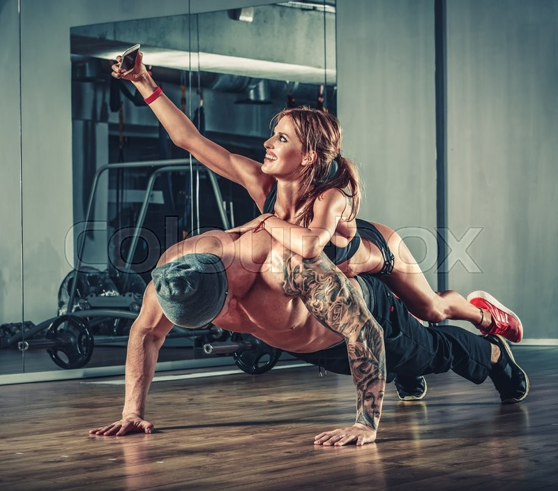 Woman with mobile phone training with muscular handsome man bodybuilder in gym, stock photo